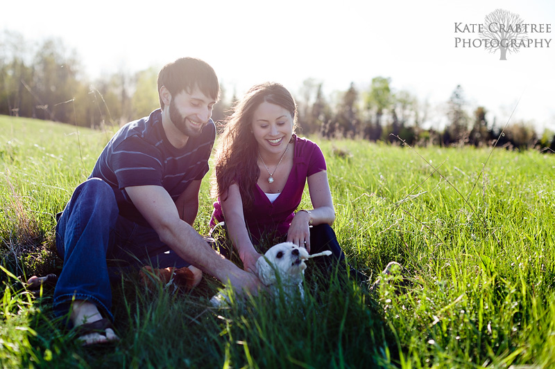 Amy and Chris play with their dog during their engagement session in Bangor Maine