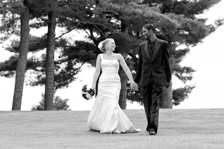Brittanie and Meko walk near the lake after their central Maine Wedding at the Lakeview Golf Course