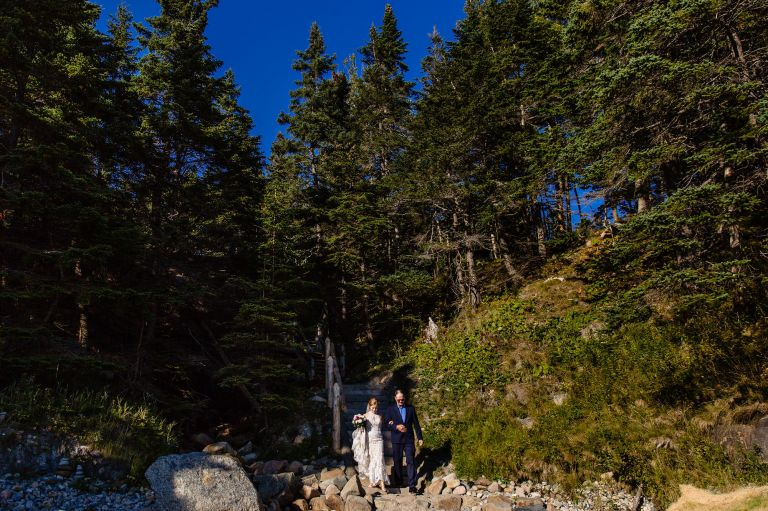A bride walks with her father at Little Hunter's Beach in Acadia toward her wedding ceremony