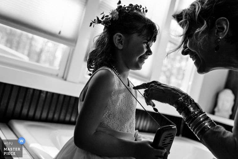 A guest plays around with a flower girl at a western Maine wedding