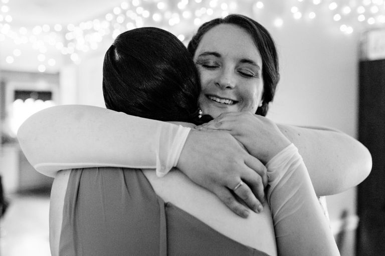 A bride hugs her sister at her Brunswick Maine elopement