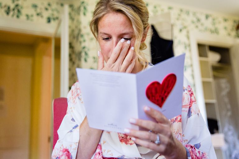 A bride cries as she reads a card from her husband to be.