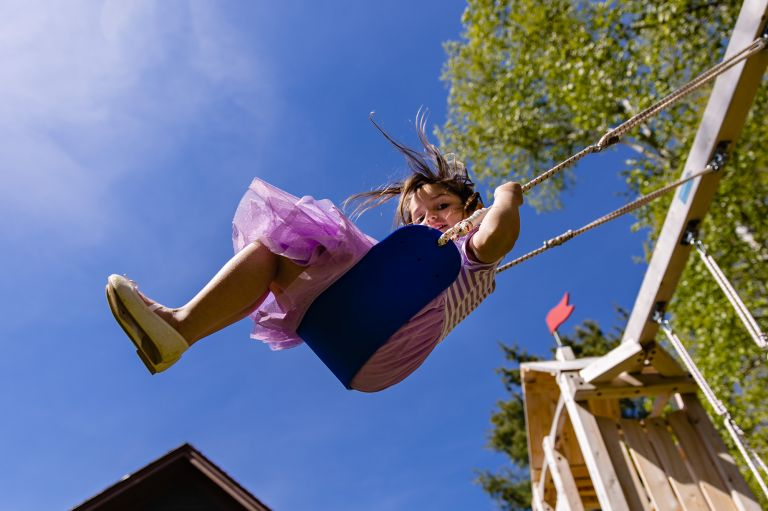 A girl swings at a central Maine wedding