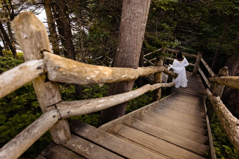 A bride walks down to the beach for her first look at her elopement in Acadia